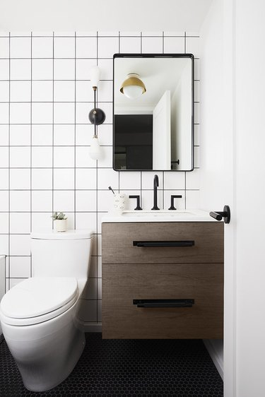 semi-flush mount bathroom light fixture with white wall tile and black penny mosaic floor tile