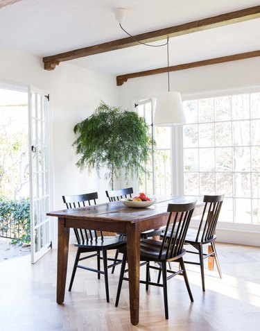 Dark wood table in airy dining room with ceiling beams