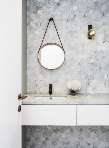 wall sconce bathroom light fixture with hexagonal wall tile and marble countertop