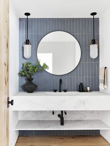 bathroom sink area with blue tiles and two hanging lights