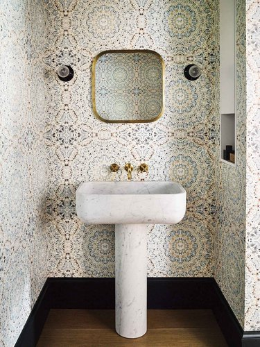 Modern bathroom pedestal  sink made from marble with wallpaper on walls