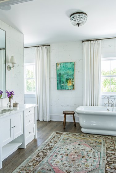 flush mount bathroom light fixture on ceiling with freestanding bathtub and white vanity cabinet