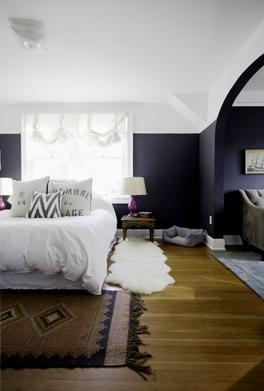 navy blue bedroom with wood flooring and area rug