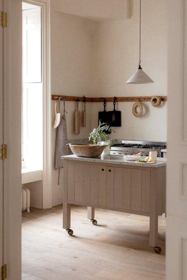 warm minimal kitchen storage idea with wooden rail
