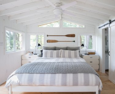 whitewashed coastal bedroom with oars above bed