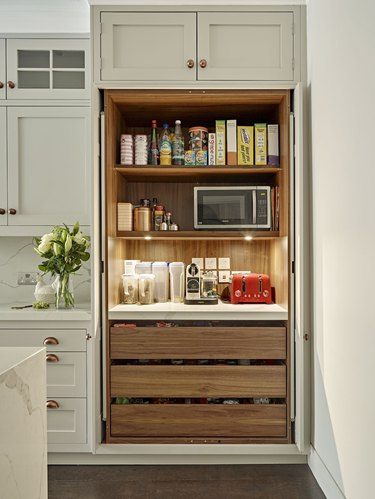 kitchen storage idea with built-in pantry closet with retractable doors and pull out drawers