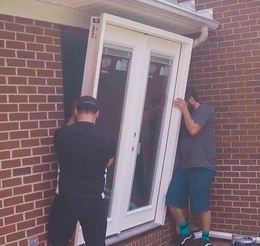 Installing a patio door in a brick wall.