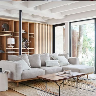 coastal sofa with wood base in living room by CB2