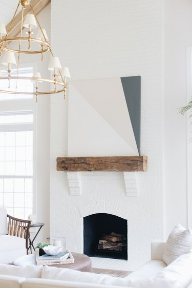 white living room with coastal fireplace and art above the mantel
