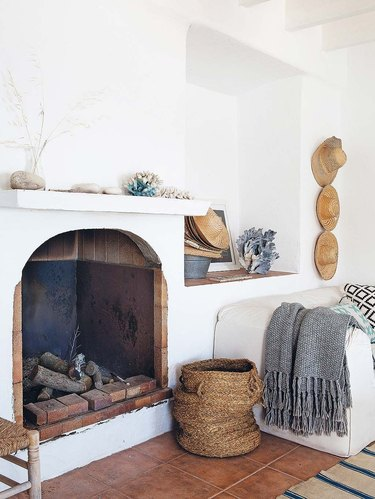 white living room with coastal fireplace and basket next to it