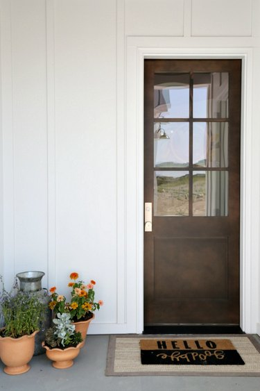 White exterior paneling surrounding wood finish front door