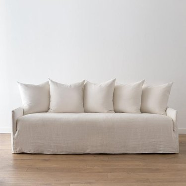 slipcovered coastal sofa with collection of back pillows by Amber Interiors