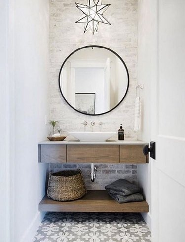 farmhouse bathroom lighting with a star shaped pendant light over a floating wood vanity and patterned floor tile