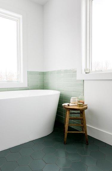 Green subway tile coastal backsplash surrounding white bathtub