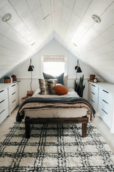 white finished attic idea for bedroom with rug and storage unites