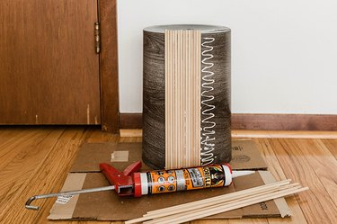 Glue the cut dowels to the sides of the trash can.