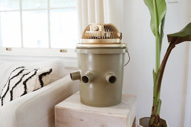 Green and gold portable bucket air conditioner on an end table next to a couch