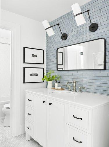 Sky blue subway tile coastal backsplash in white guest bathroom