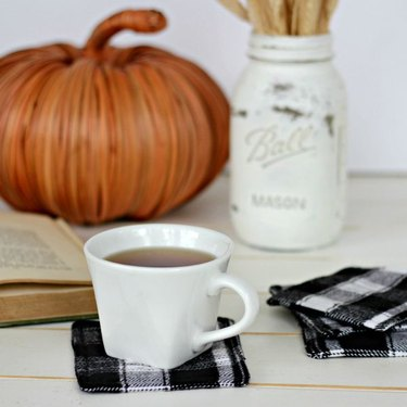 DIY fall decor idea with cup of coffee on a tabletop with flannel coasters