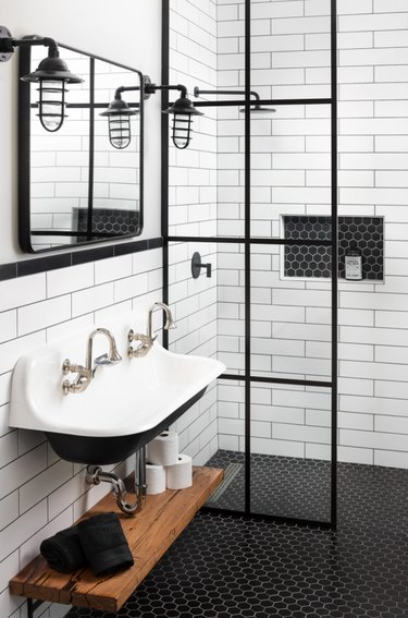 farmhouse bathroom lighting with cage style wall sconces mounted to white shiplap walls with black mosaic penny tile and trough sink