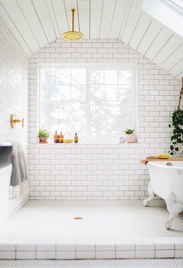 white finished attic idea for bathroom with subway tiles and clawfoot tub