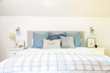 Upholstered headboard with brass sconces and many pillows on bed.