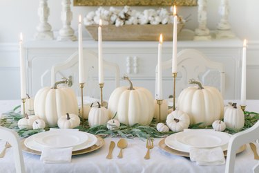 DIY fall decor idea with white pumpkin centerpiece on white tablecloth table with taper candles