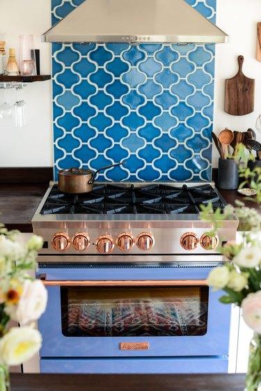 Dark blue coastal backsplash in fish scale shapes with blue stove
