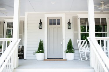 craftsman with gray exterior paint on siding and front door and plants on the porch