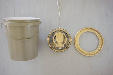 Plastic bucket painted olive green and fan painted gold