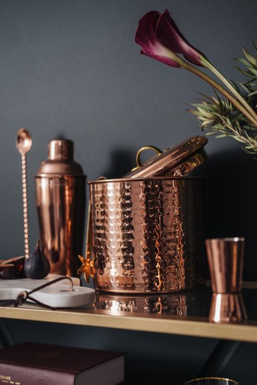 Copper barware, including ice bucket, cup, and mixer.
