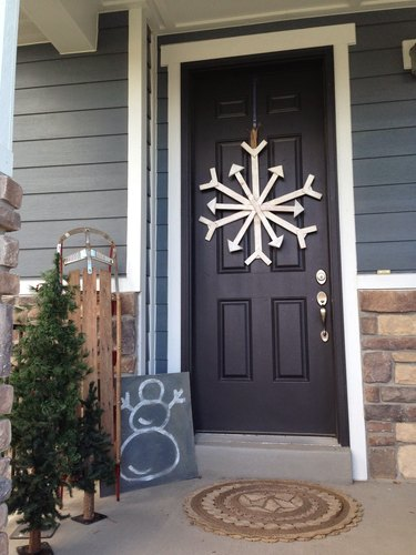 Christmas Door Decorations on Black front door with hand made snowflake, chalk board with snowman, small Christmas tree.
