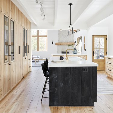 hardwood kitchen flooring in rustic space with wood cabinets and black island with white countertops