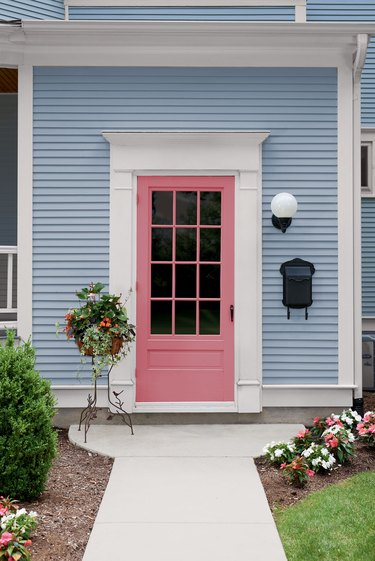 pink front door on light blue house