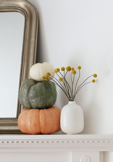 modern fall decor on fireplace mantel with stack of pumpkins on the mantel