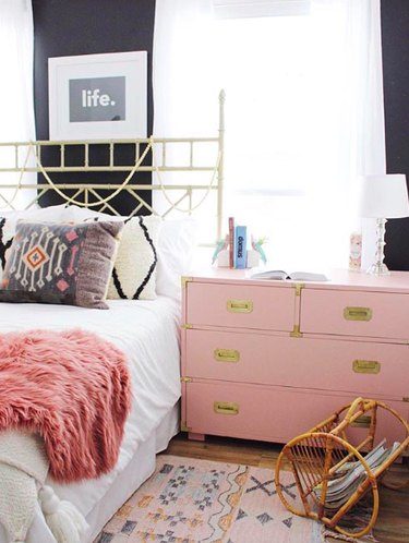 bedroom with pink dresser and faux fur bed throw