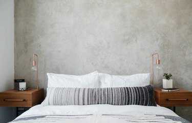 industrial bedroom with concrete walls and copper table lamps