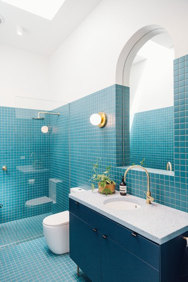 blue tile bathroom with deck-mounted faucet on blue vanity
