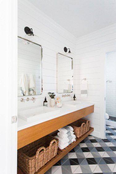 patterned floor tile and shiplap walls with farmhouse bathroom lighting
