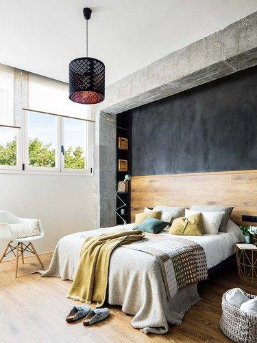 industrial bedroom with wood headboard and flooring