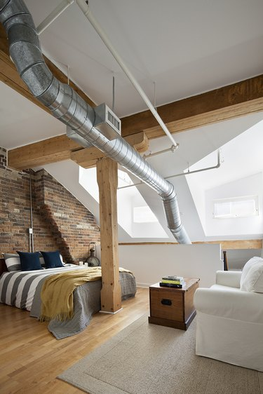 industrial bedroom with exposed ductwork and wood ceiling beams