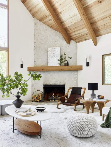 modern fall decor in white living room with fireplace and wooden ceiling