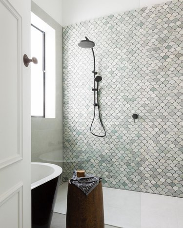 Handheld showerhead in walk-in shower with green mosaic wall tile and freestanding bathtub