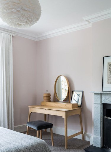pale pink bedroom with wood vanity table and fireplace