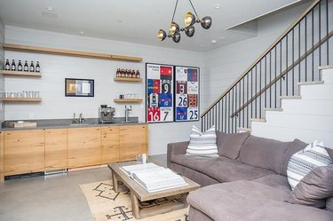 basement ideas Gray sectional couch, concrete floors, wet bar with light wood cabinets, modern chandelier, stairway, area rug.