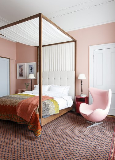 pale pink bedroom with four-poster canopy bed and Egg chair