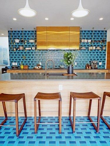 blue and gold kitchen color scheme with blue tile backsplash and patterned floor
