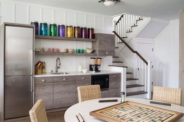 basement ideas with Stainless steel fridge and gray wood cabinets with open shelves, sink, round card table, stairway.