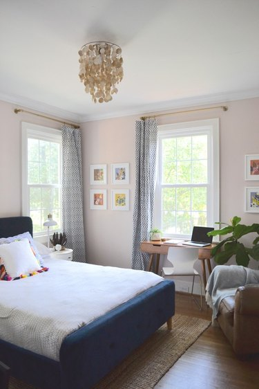 light pink bedroom with blue bed and accent chair