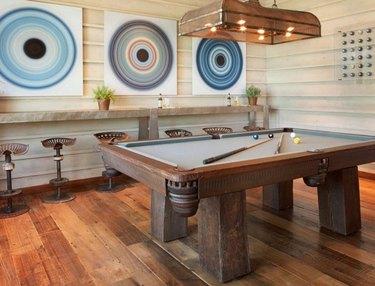 basement ideas with Rustic wood pool table, wide plank wood floors, industrial bar stools, pool ball art prints, light over pool table - pool table lamp.